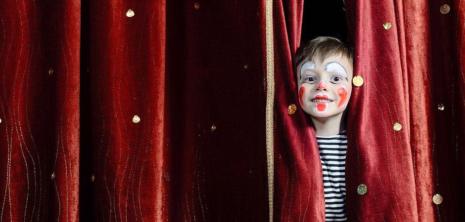 Young Boy Wearing Clown Make Up Peering