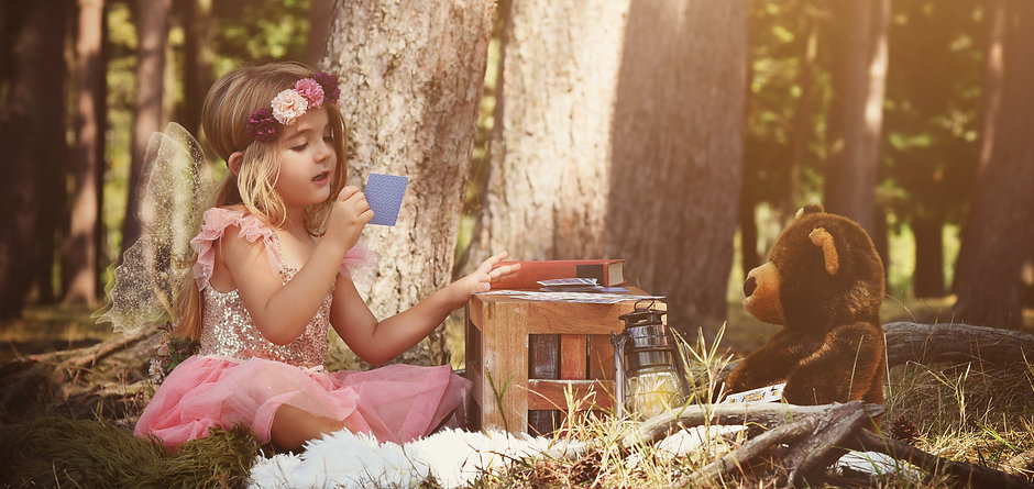 A little girl is sitting in the woods pl