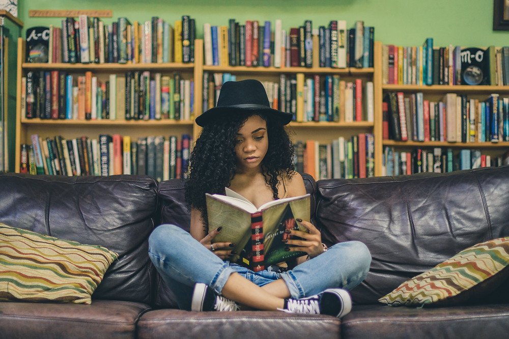 A young woman reading on a couch in front of a bookshelf