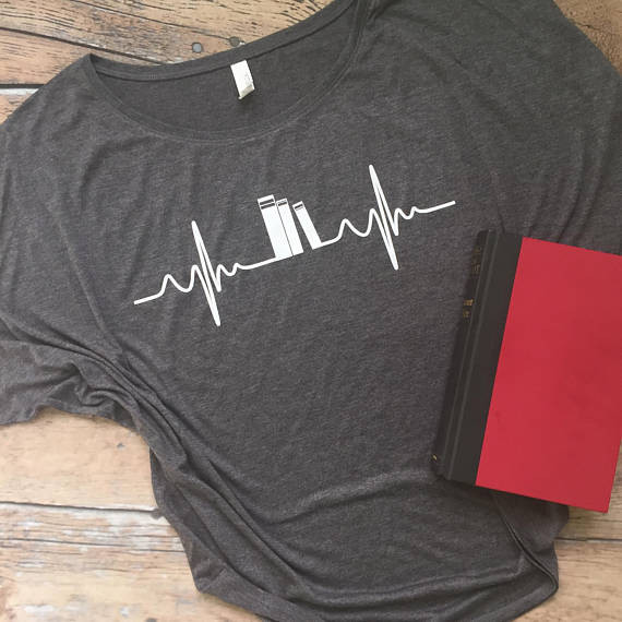 Grey t=shirt with illustration of three books forming the mid section of a heart beat