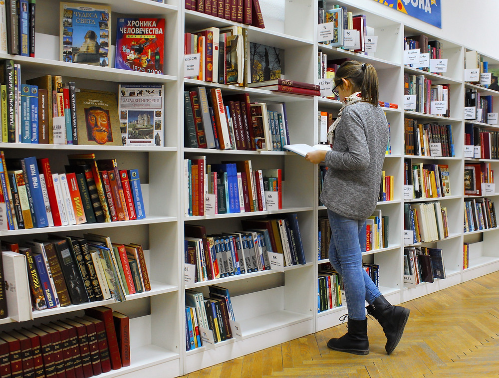 A woman browses a bookshelf at a bookstore