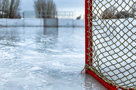 a view of a hockey rink from behind one of the nets