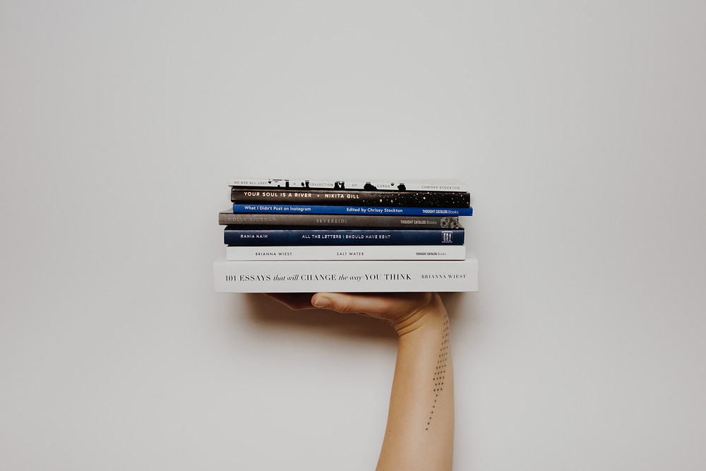 A hand holding up a stack of books