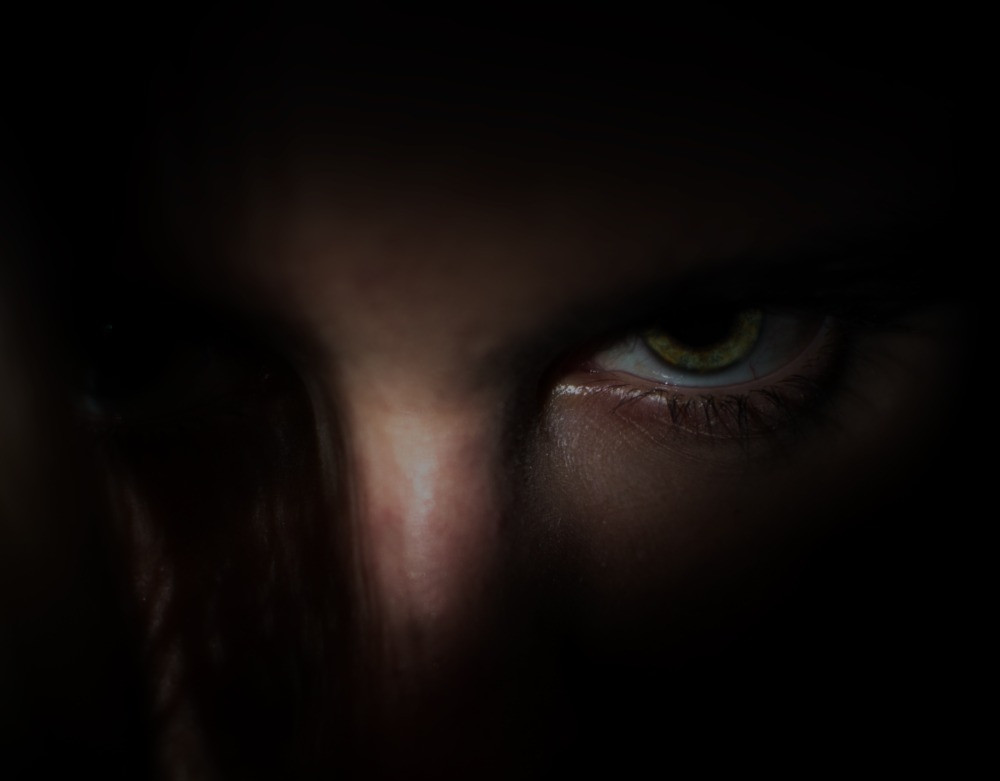 A woman's face shrouded in darkness so only her eye is visible