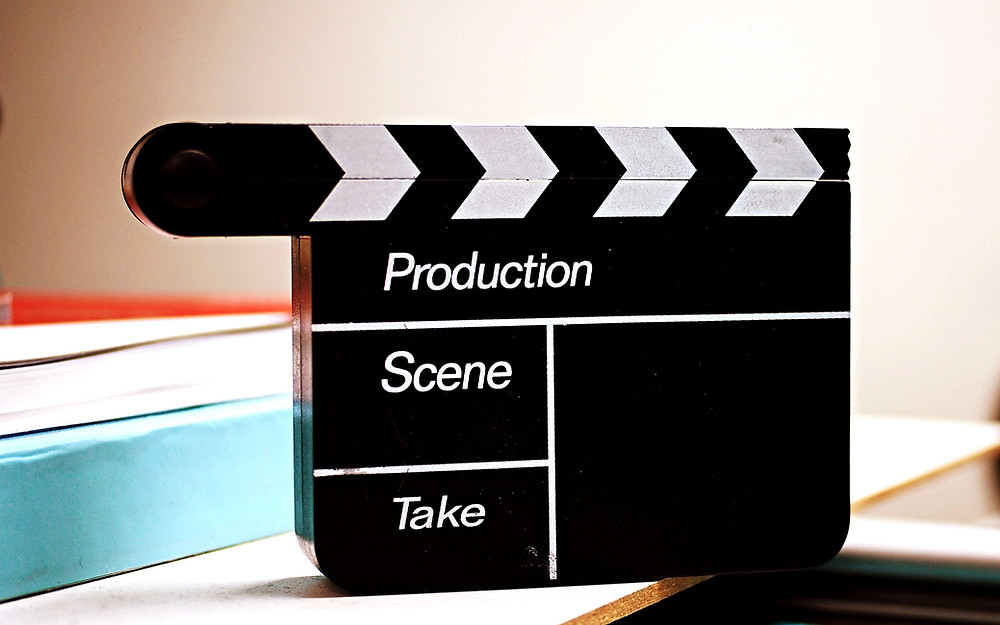 A blank clapperboard sits on a desk