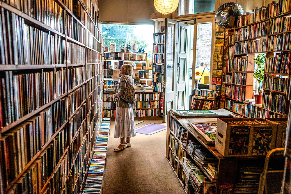 A woman with a backpack browses through full bookshelves in a bookstore