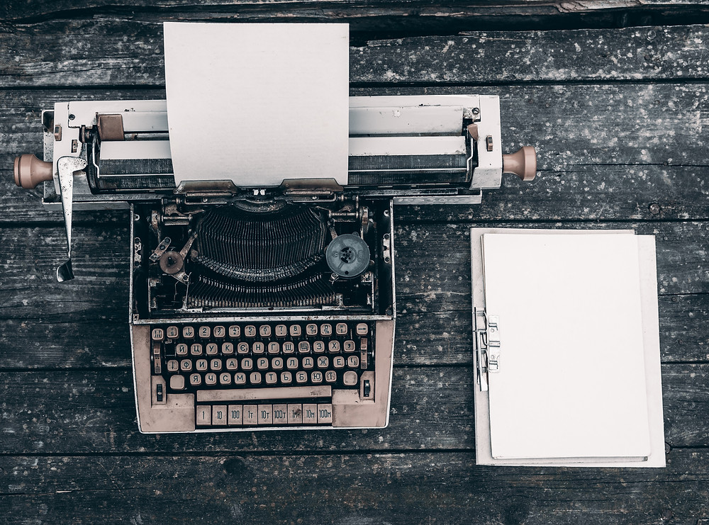 a typewriter next to a notepad