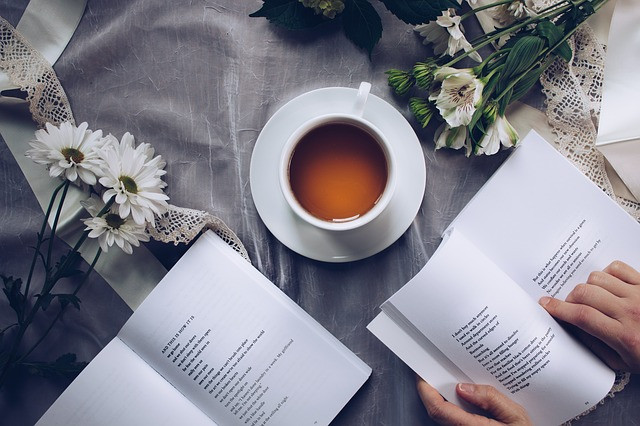 Overhead view of a person enjoying a poetry book and a cup of tea