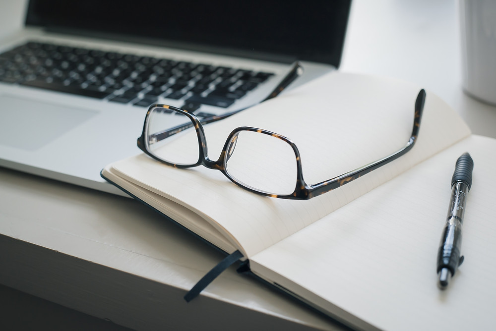 A pair of glasses sit upon an open notebook beside a laptop