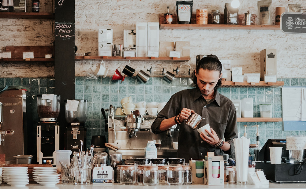 A brown haired man makes a cappuccino at the counter of a coffee shop