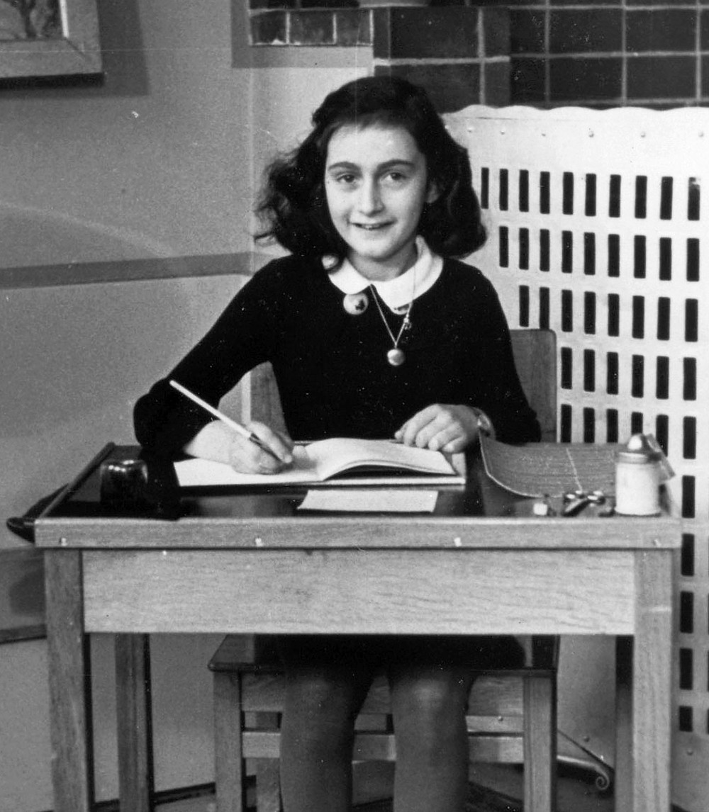 Anne Frank writes at a desk