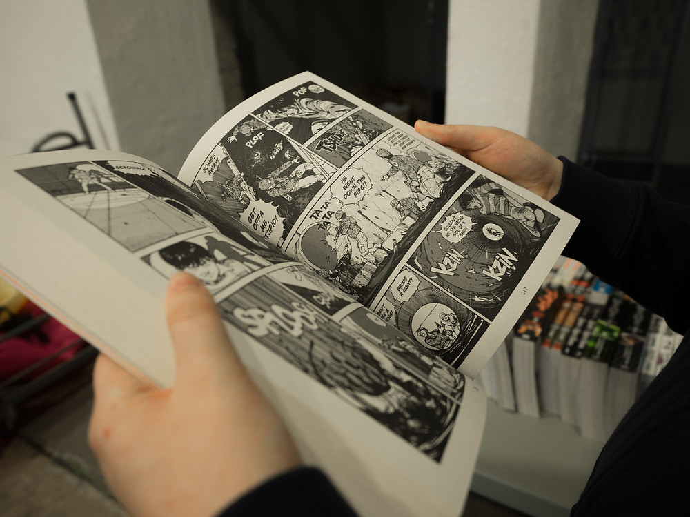 Hands holding a graphic novel open