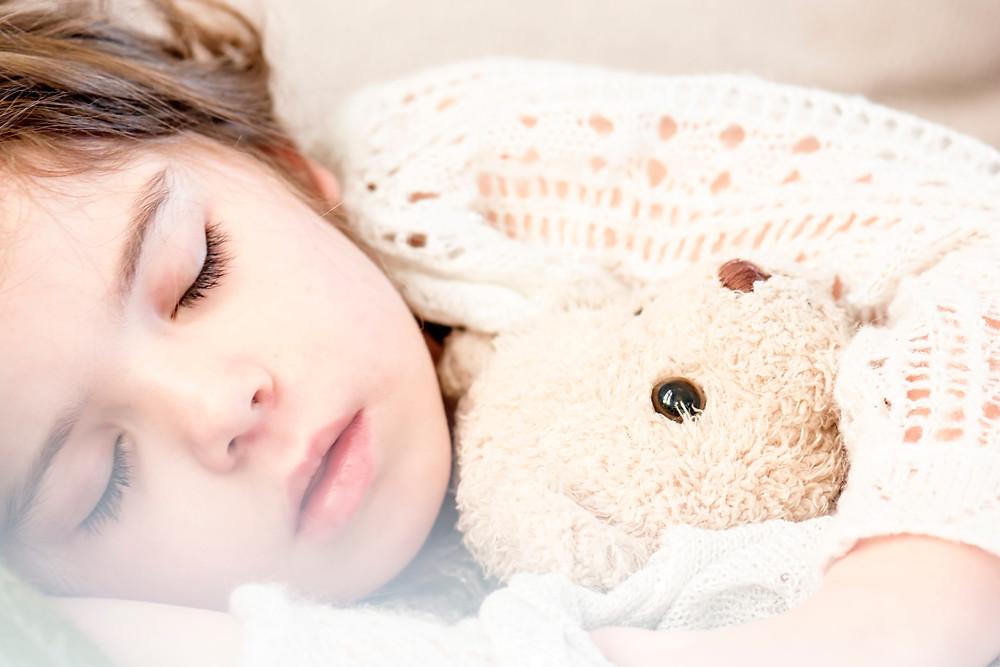 A child sleeps with a teddy bear