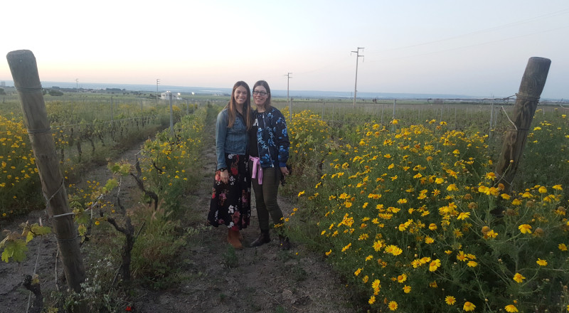 Two women, Katarina Andersson and Marzia Varvaglione, standing next to flowers in Puglia.