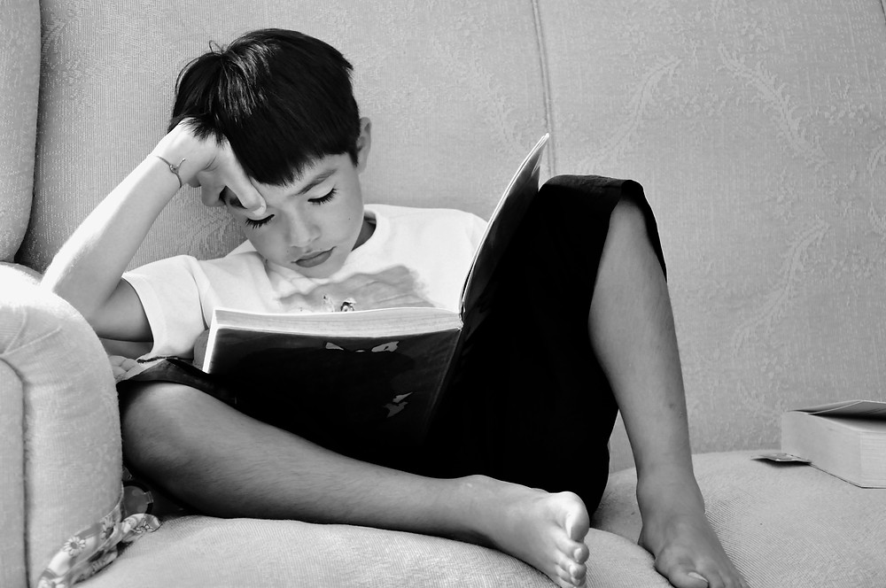 Child sitting on a couch peacefully while reading a book