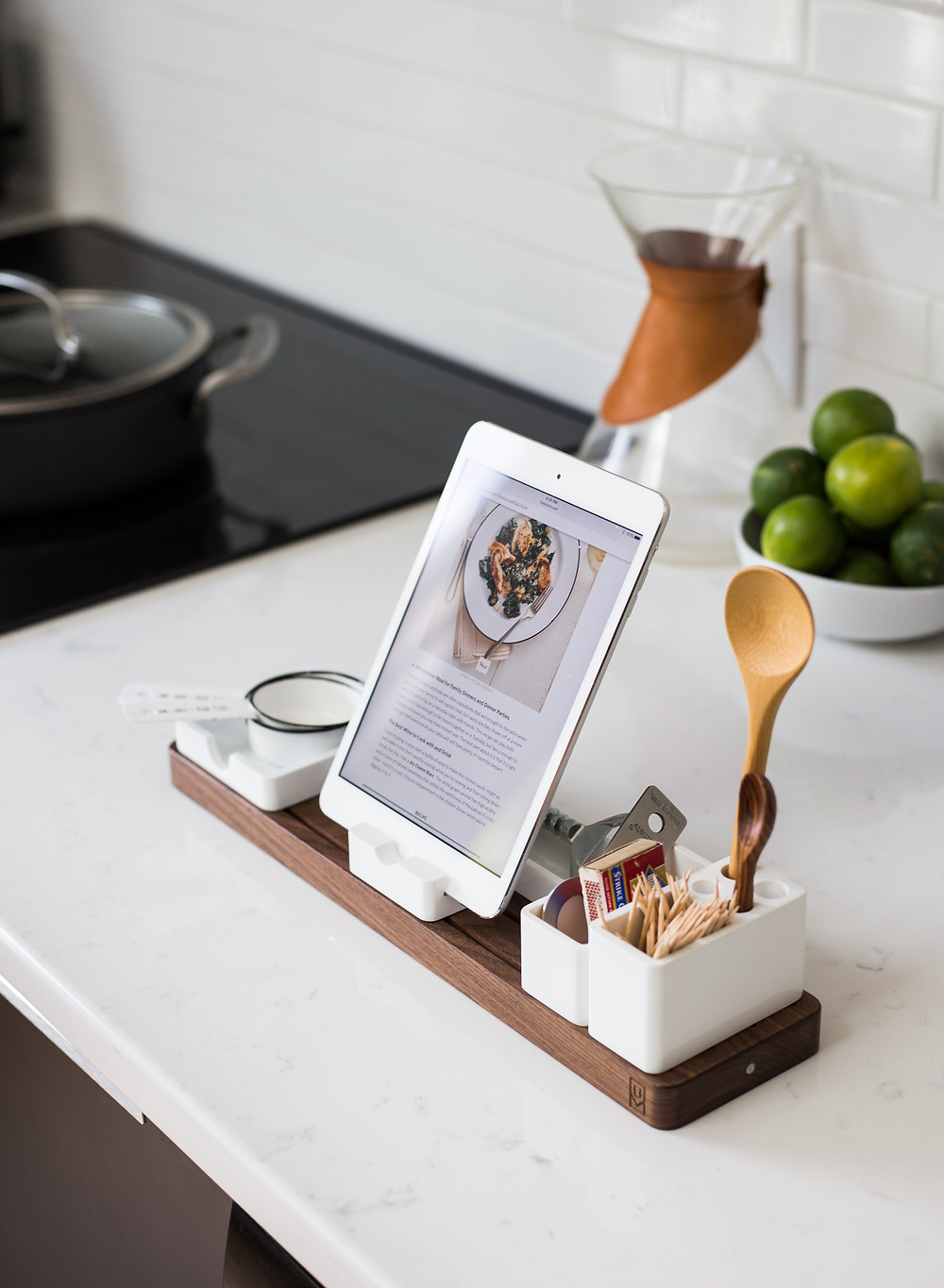 An iPad, with a cooking blog on screen, set on a stand with cooking tools