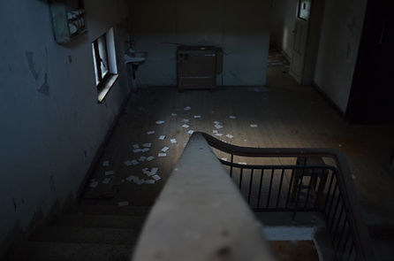 A dimly lit staircase in a creepy, decrepit house