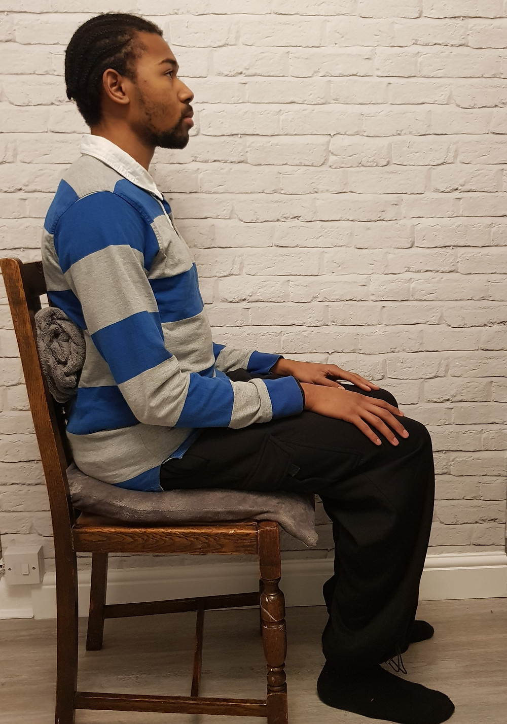 An individual sitting on a cushion to elevate his hip over knee. Also has a towel in the small of his back to encourage an anterior pelvis tilt