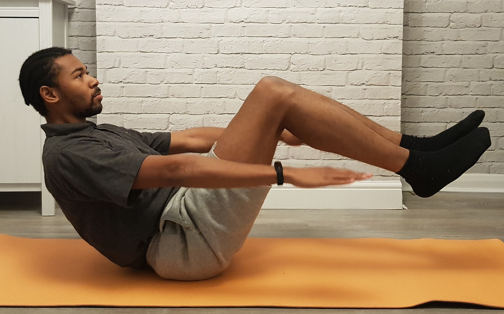 An individual doing the dead bug pose as part of a home work out.