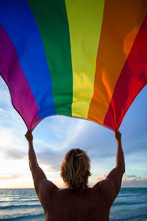 Man holding a fluttering rainbow gay pri