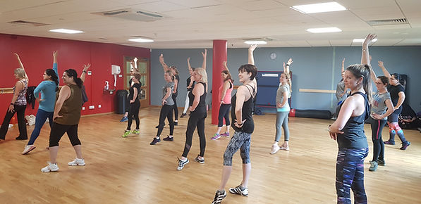 Ladies participating in a dance fitness class at a health and fitness club.