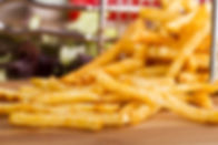 Tasty french fries on cutting board, on