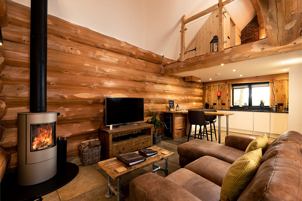The inside of a log home showing wood burning stove and homely atmosphere