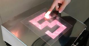 Novel tactile display using computer-controlled surface adhesion