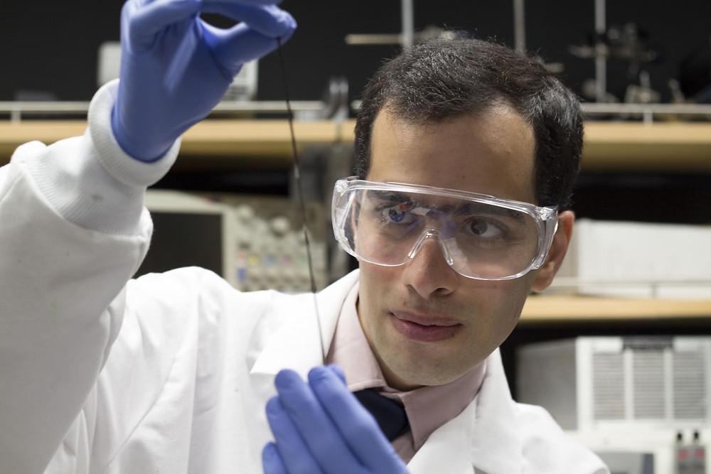 UBC doctoral student Hossein Montazerian takes a close look at a tiny sensor embedded into a fibre.  @ UBCO Okanagan