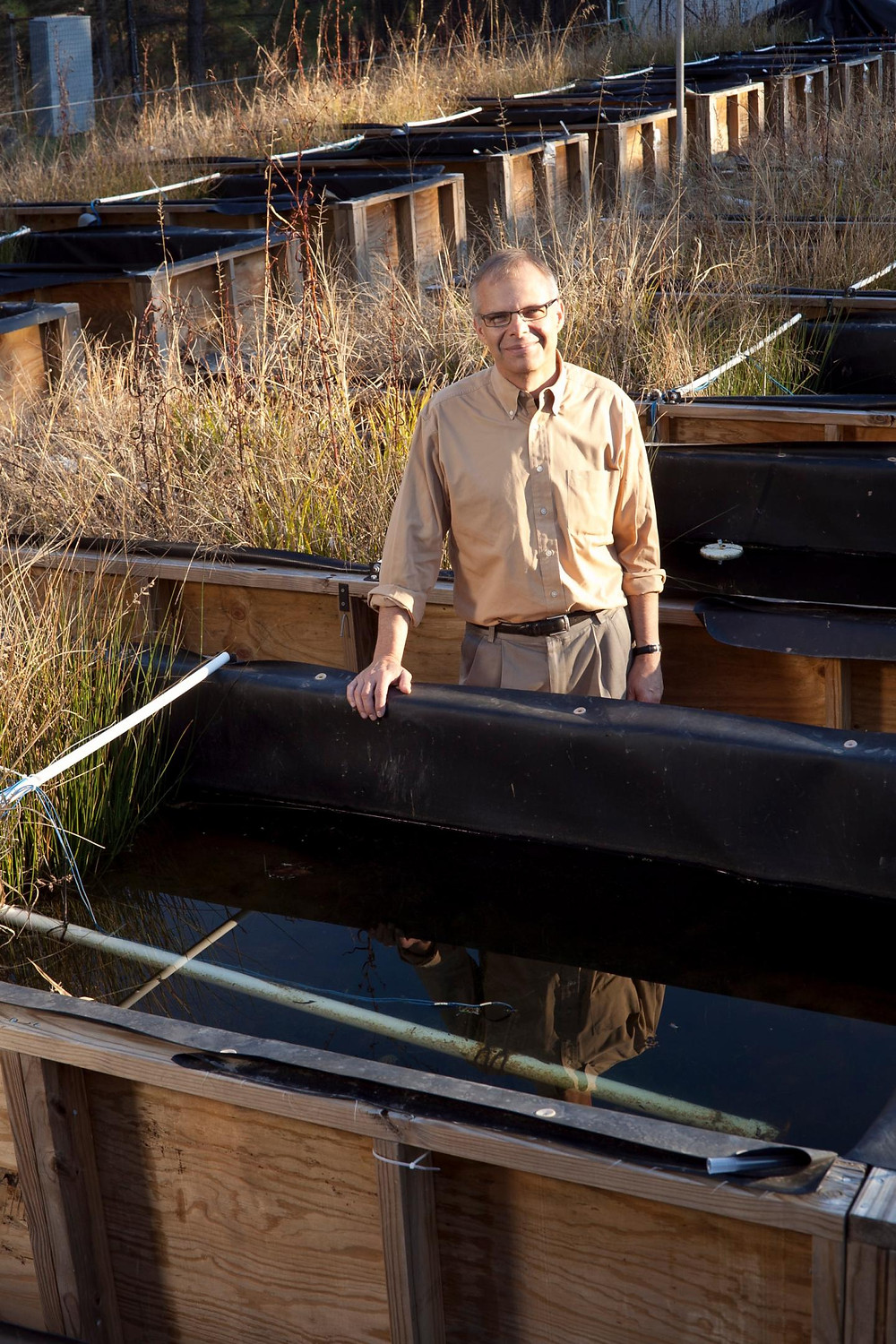 Mark Wiesner stands with rows of mesocosms -- small, manmade structures containing different plants and microorganisms meant to represent a natural environment with experimental controls. @ Duke University