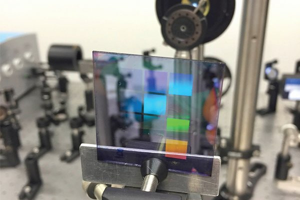 It contains ten patches that each have their own silver nanoparticle pattern. The colors on the sample are not the laser light (the laser is not on) but reflections, similar to the colors that can be seen on the surface of a compact disk. @ Alexei Halpin, Eindhoven University of Technology.