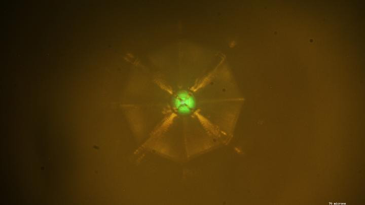 Scientists bombarded a sample of a new superconducting material with X-rays to study its structure at the Advanced Photon Source at Argonne National Laboratory. The X-ray fluorescence creates the greenish color at the sample (center).  @ Drozdov et al.