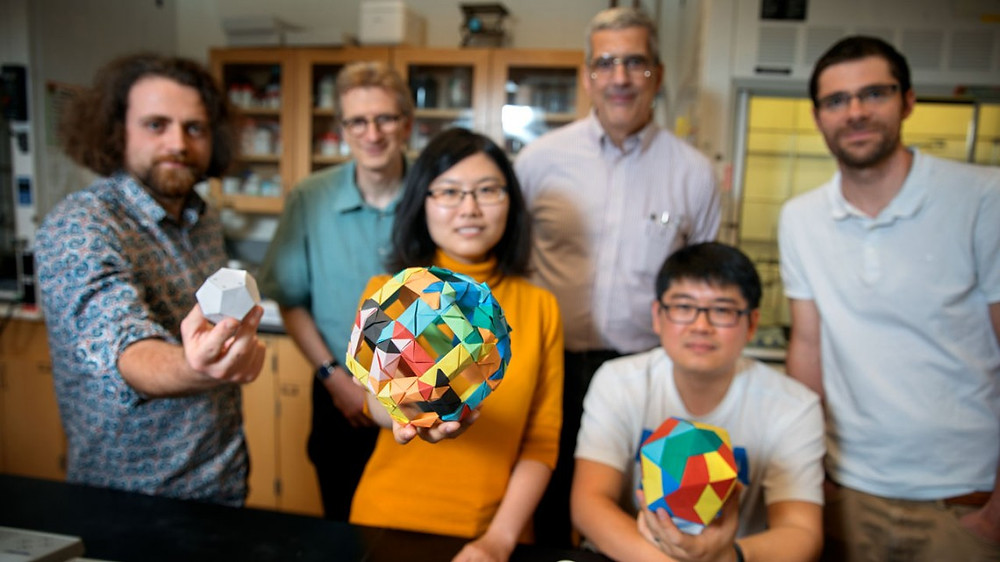 Doctoral student Melik Turker, left, holds a model of a dodecahedron in the lab of Ulrich Wiesner. Also pictured are doctoral student Yunye Gong, center, holding a model of a cage structure, and postdoctoral researcher Kai Ma, holding an icosahedron. The group's paper on their discovery of nanoscale 12-sided silicon cage structures published recently in Nature; in the back row, left-to-right, are Wiesner, engineering professor Peter Doerschuk and postdoc Tangi Aubert. @ Lindsay France
