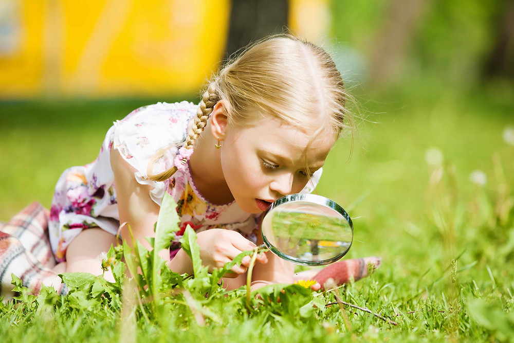 Child looking at the ground through a magnifying glass