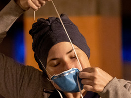 Emergency Department nurse Christa Duran carefully puts on a slightly used face mask before starting her morning shift at San Francisco General Hospital in San Francisco, Calif. Saturday, April 11, 2020. Duran has decided to reuse masks that aren't particularly soiled to preserve personal protective equipment.