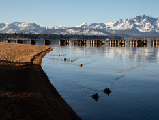 Ducks glide across glassy waters as mountains dusted in snow are seen South Lake Tahoe, Calif. Thursday, December 10, 2020. Vacation travel to Lake Tahoe will be banned for at least three weeks starting Friday due to a regional rise in the number of COVID-19 hospitalizations.