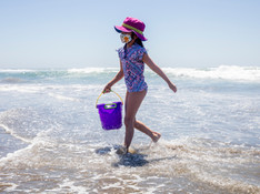 A young girl from Campbell (no name given) sports a mask while frolicking in the water at Ocean Beach in San Francisco, Calif. Monday, May 25, 2020. The warm Memorial Day weather brought out large crowds to popular parks and beaches despite the shelter-in-place order amid the COVID-19 pandemic.