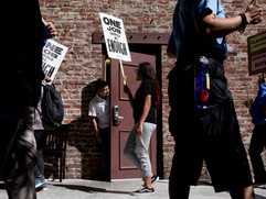 A restaurant worker pokes his head out of a nearby door to watch as Union Local 2 members, Flagship cafeteria contract workers and supporters march with signs during a protest held outside of the Facebook offices in San Francisco, Calif. Tuesday, July 16, 2019.