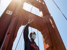 A demonstrator raises his fist in the air while sporting a mask as he makes his way with thousands of others across the Golden Gate Bridge in San Francisco, Calif. Saturday, June 6, 2020 during a march in support of the Black Lives Matter movement.