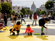 """(From left) Ashley Williams, her 10-year-old daughter Marley McNealy and Williams' sister Mo McNealy work alongside volunteers and staff African American Art & Culture Complex work to paint massive letters spelling """"Black Lives Matter"""" across Fulton Street between Webster and Octavia streets in San Francisco, Calif. Friday, June 12, 2020.   """"I thought it was important as an SF native to show support for community because there aren't that many Black natives left"""" says Mo. """"For me, it's paying homage to that because that was done purposefully. I'm honoring my childhood friends. People don't understand when you aren't from here you get to go back to your hometown and the people you grew up with are still there. But for me, it's not the same and it's hurtful to know that this government has done Black residents so bad. And I will continue to fight for our black residents because I miss my community."""""""