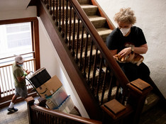 Kristin Demoro sits on the stairs with her cat Twinkie as movers work to remove boxes from her packed-up apartment in Oakland, Calif. Tuesday, April 21, 2020. Demoro is moving to Washington state to be close to her mom after being laid off due to the Coronavirus outbreak and shelter-in-place, but she has a really extensive family history and lineage in San Francisco and never thought she'd leave. Her father, Harre Demoro, was a famed San Francisco Chronicle reporter, her grandfather was born in 1900 in San Francisco.