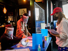SF Eagle leather bar owner Lex Montiel (left) helps Christine Malvin (right) retrieve her ballot and vote in-person through a plexiglass barrier at SF Eagle in San Francisco, Calif. Tuesday, November 3, 2020. Bay Area residents headed to the polls on Election Day morning to cast their vote in local and national elections. Polling places are expecting less in-person voter this year due to the increase in mail-in and drop-off ballots.