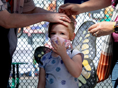 Colette Youkin-De Luc, 4, sports butterfly wings while her parents Amiee Le Duc (right) and Dana Younkin help her put on a mask before being tested at a Coronavirus testing site for Mission district residents at Cesar Chavez Elementary School in San Francisco, Calif. Saturday, April 25, 2020. UCSF is providing free testing for Coronavirus and its antibodies to members of the Latino community at four locations across the city starting Saturday.