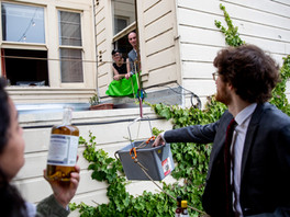 Alexis Bustos and Matthew Stein (foreground) fill up a bucket with cocktail ingredients, snacks and other communal goods to send over to Sarah Hingston and Tom Broxton (center) as they use a rope to pull it to window of their apartment in San Francisco, Calif. Saturday, June 20, 2020. Since the shelter-in-place order was implemented, these neighbors began holding a weekly happy hour named Bucket Bar from the windows of their homes to promote social distancing while still being social.