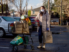 A mother of an infant from San Carlos (no name given) poses for a portrait while wearing a protective mask and gloves after shopping for her groceries from Draeger's Market in Menlo Park, Calif. Tuesday, March 17, 2020. As of Tuesday, six counties in the Bay Area have been ordered to shelter in place in an attempt to prevent the spread of the Coronavirus.