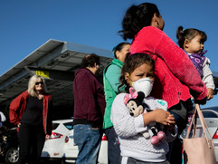 Addison Bernal, 5, wears a mask while she stands in line with her mother, Anahi Bernal and sister, Camilla, 3, while for the Redwood Empire Mobile Food Bank parked at the Kaiser Permanente parking lot in Santa Rosa, Calif. Wednesday, Oct. 30, 2019.