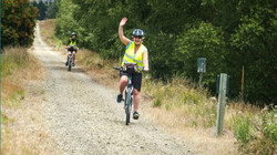 cyclist-waving-while-riding-along-old-rail-trail