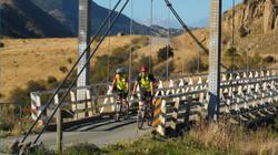 Cyclists riding across the bridge