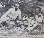 family-picnicking-on-a-blanket-in-countr