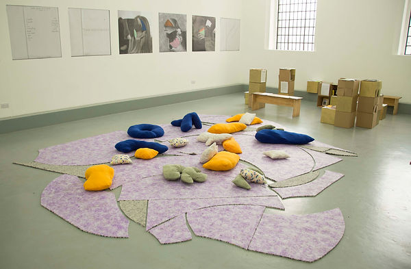 Image is of an exhibition in a white walled gallery space. There are no people, just the artworks. In the foreground is a floor piece which is made up of purple and grey underlay in a sort of jigsaw like formation.The shapes are irregular, some edges round, some straight. On top are a range of cushions of different quasi-organic shapes. They are marigold yellow, navy blue and irredescent patterned. In the far end there is a library made up of benches and cardboard boxes spray painted gold. On the wall are a mixture of images. Some collages of different body parts with small highlights of colour (orange, blue, teal and pink), the images of text are out of sketchbook pages and are handwritten, you cannot make out the text from the viewpoint of the camera. These imags are approx 1x1m 5 line a long wall to the left.